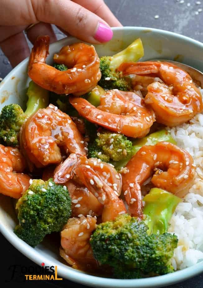 instant pot chinese shrimp and broccoli served with white jasmine rice in a light blue bowl
