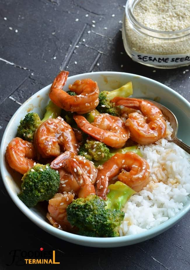 instant pot shrimp and broccoli served with white rice in a light blue bowl with a spoon