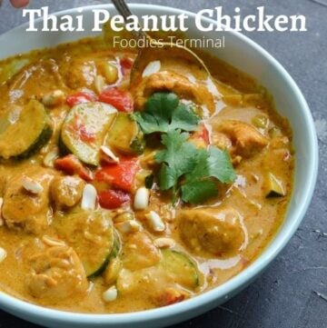 Thai Peanut butter chicken curry in a light blue plate with a spoon & garnished with cilantro & roasted peanuts