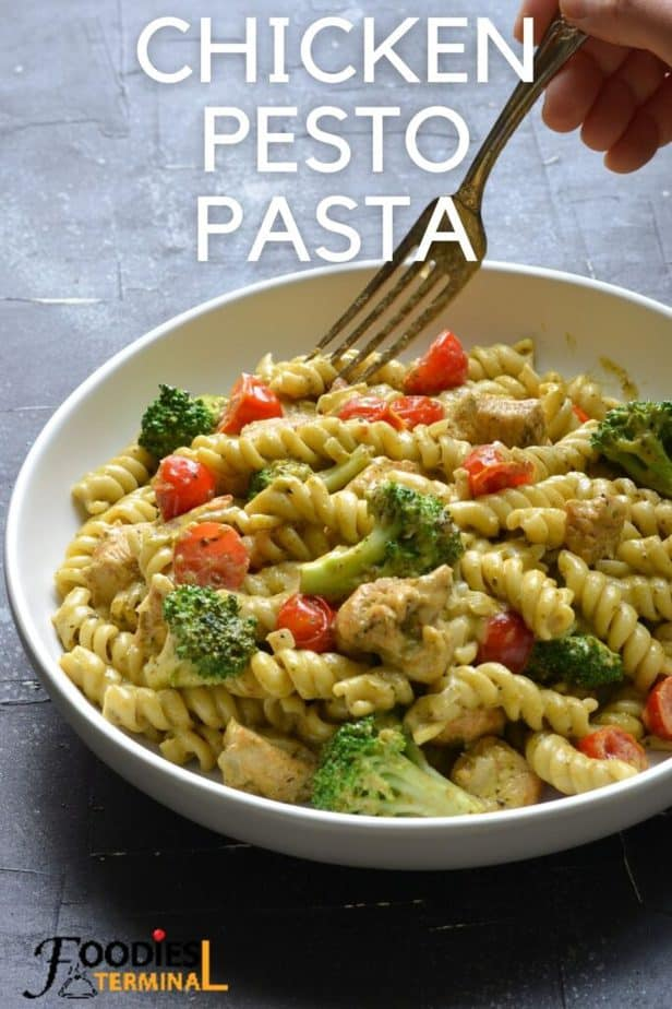 instant pot pesto chicken pasta recipe with cherry tomatoes & broccoli in a white bowl with a fork
