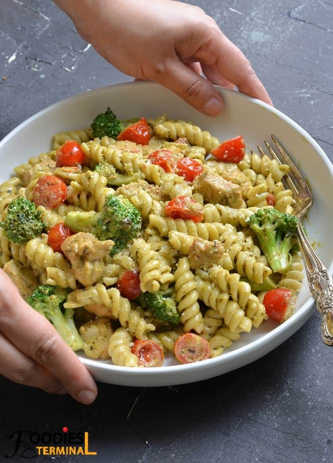 best creamy pesto pasta chicken in a white bowl with a silver fork